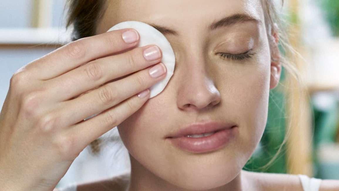 Cô gái dùng bông tẩy trang tẩy sạch lớp phấn mắt